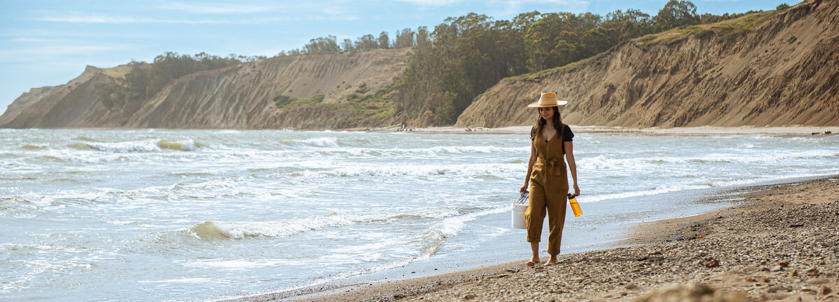Woman in orange overalls and a hat walking on the beach holding a bucket and orange water bottle picking up trash