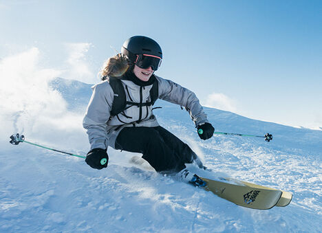 A person skiing down hill on snow.