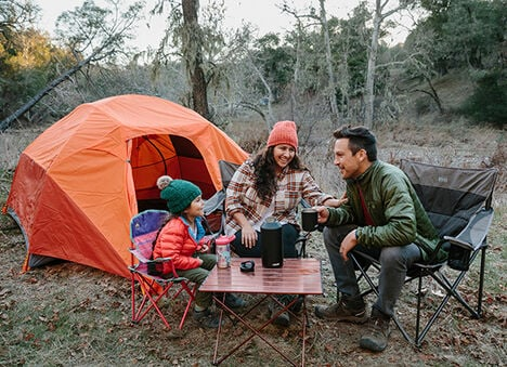 Image of a woman, man, and child outside of a tent.