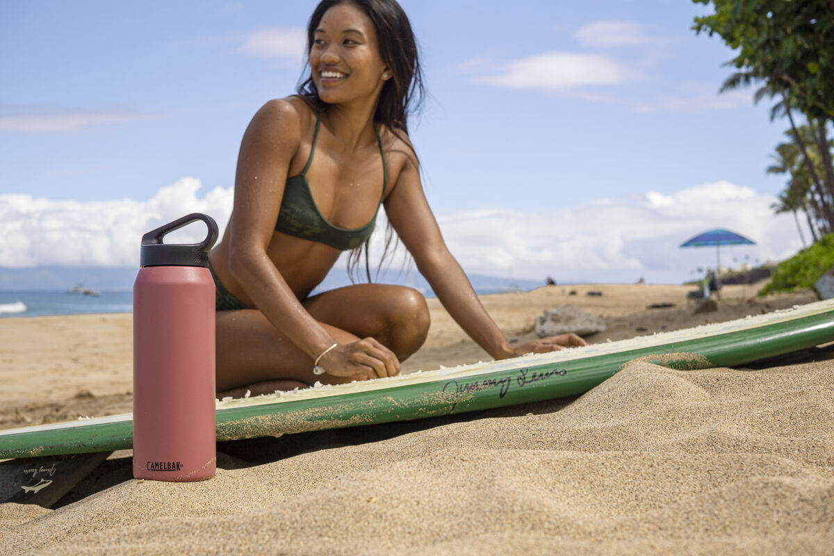 Woman with surfboard next to a stainless steel water bottle.