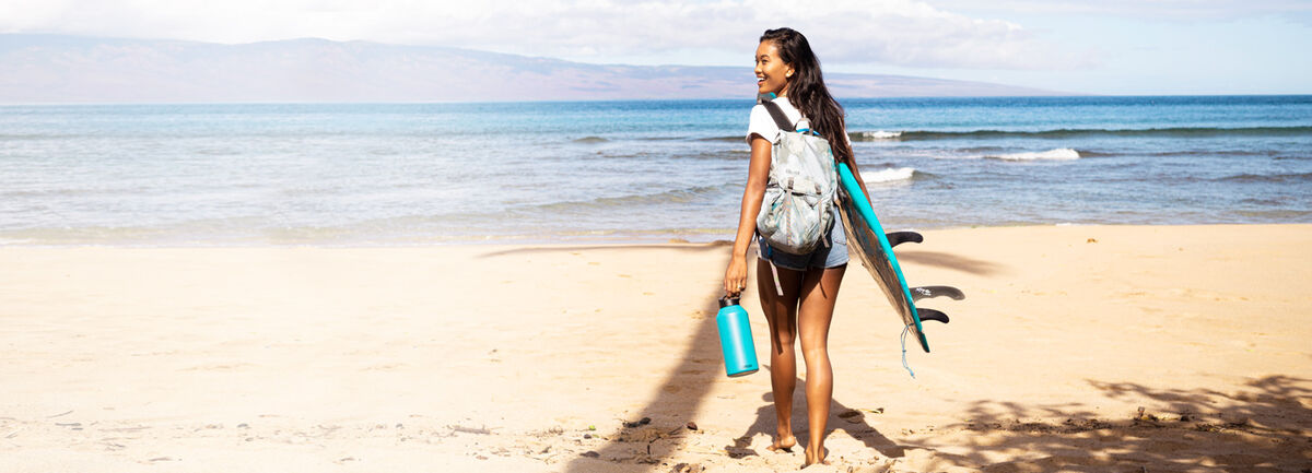 Woman with surf board and water bottle walking on the beach.