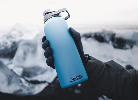 Reusable water bottle with ice in background.