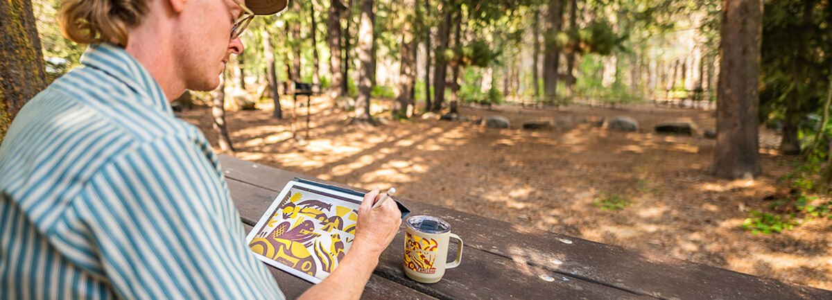 man wearing striped serch sitting at picnic table outside drawing design on ipad with mug nearby