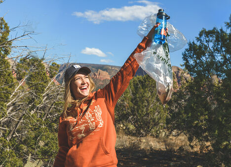 Woman holding up Earth Day Water Bottle and Clean Up Kit.