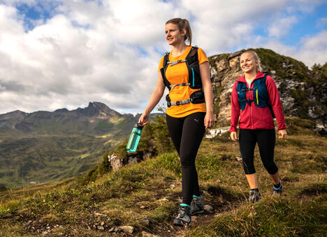 Two Women Hiking and Carrying Water Bottles.