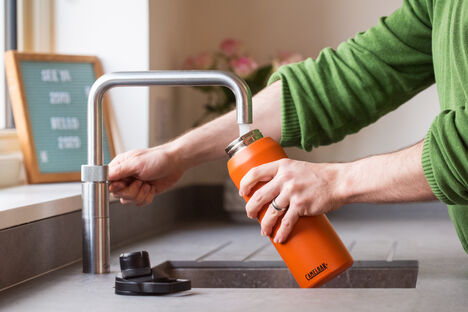 Reusable water bottle being refilled.