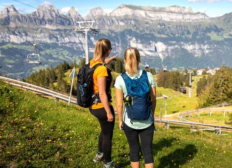 Two women wearing hydration backpacks.