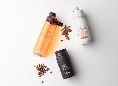 Two custom water bottles and one custom travel mug with coffee beans.