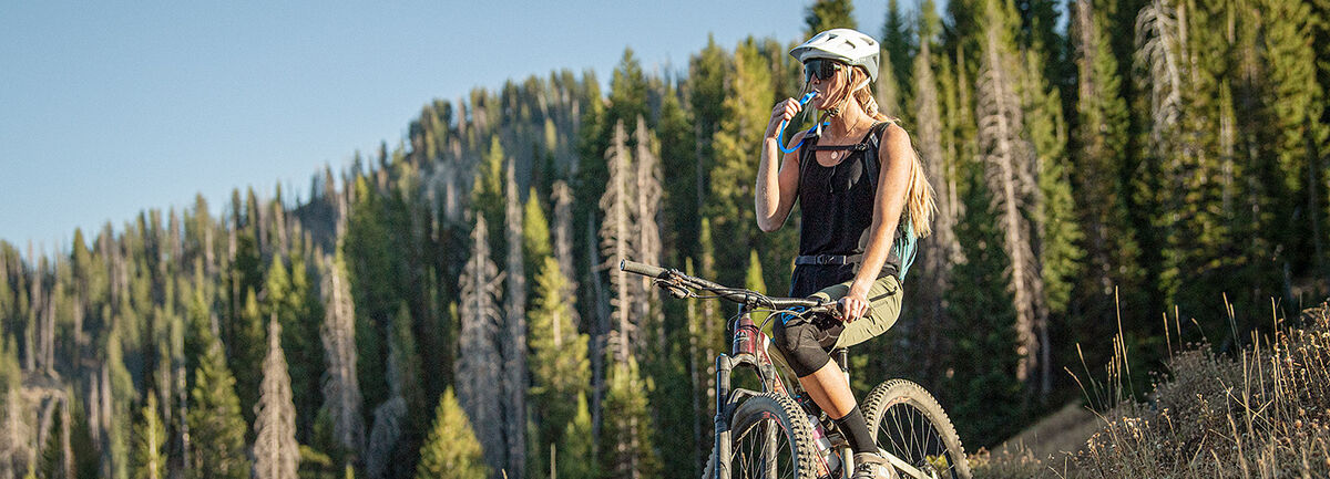 woman looking at the view on a mountain while on a mountain bike sipping out of a reservoir pack.