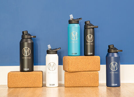 Five custom stainless steel water bottles with yoga blocks on a blue background.