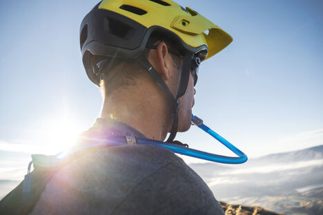 Man in bike helmet drinking water from a hydration pack.