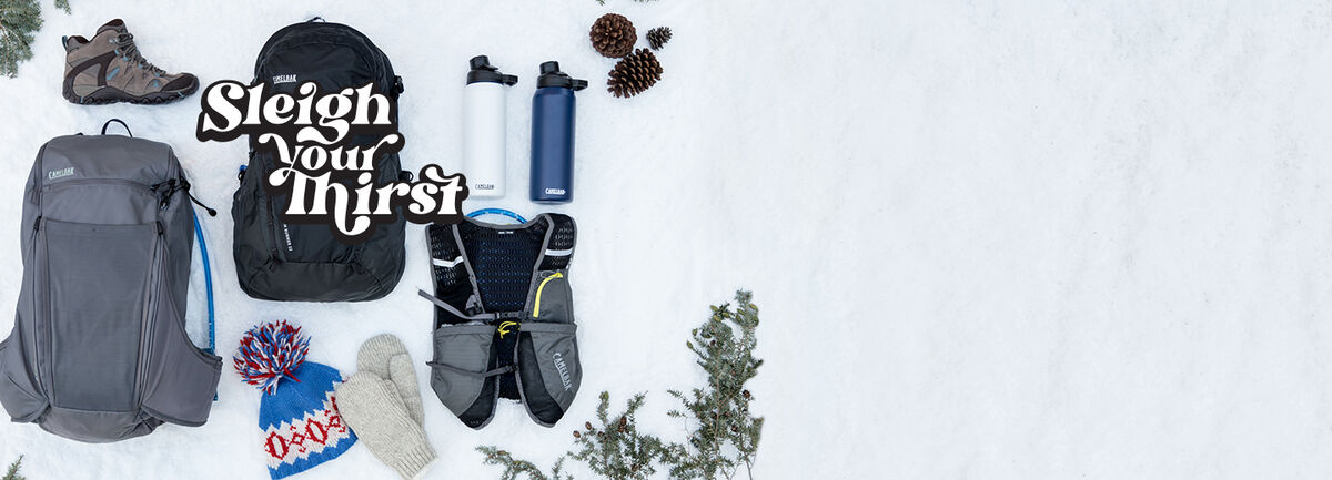 Selection of hydration backpacks, running vest, and water bottles on a snowy background.