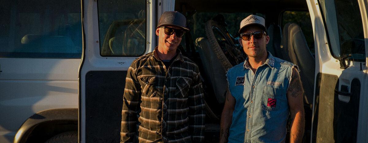 Two men in ball caps standing in front of an open van.