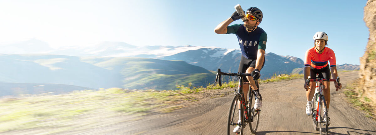 Two Bikers on Mountain drinking from a Podium Bottle.