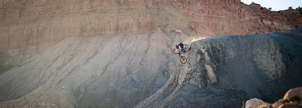 Mountain biker riding down a steep cliff.