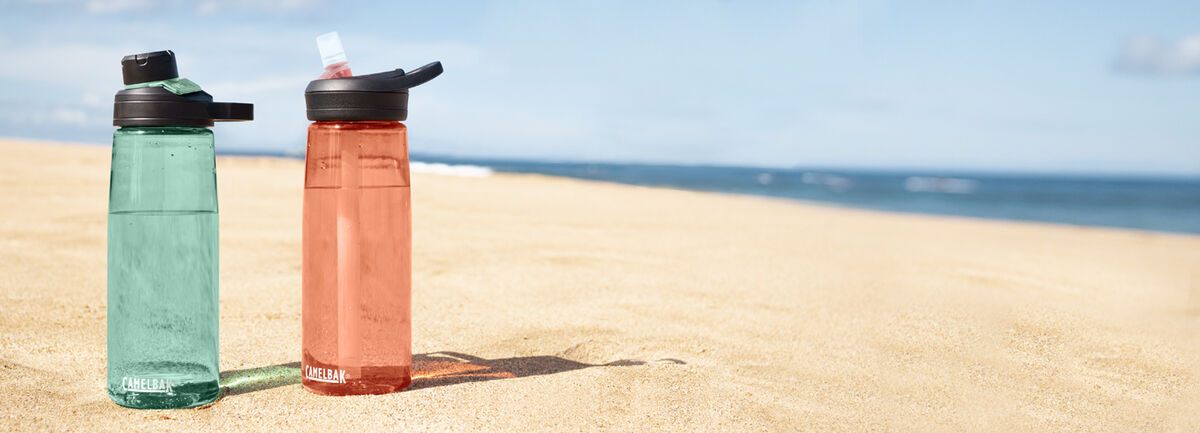 Two Tritan™ Renew Bottles in the sand on a beach.