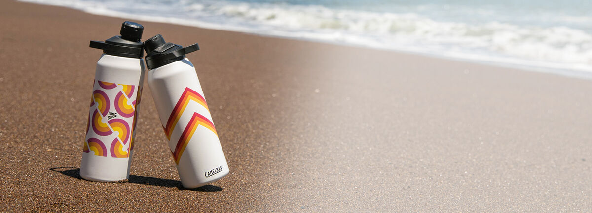 Two Stainless Steel water bottles on the beach.