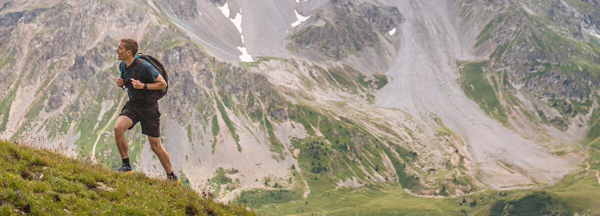 Hiker wearing a hydration pack on a mountain.