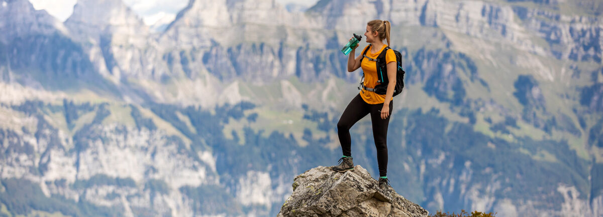 Female Hiker standing at the top of a peak drinking from a water bottle.
