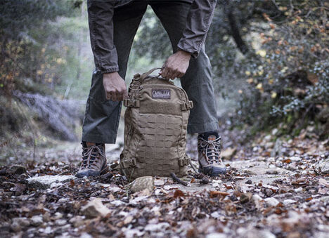 Military pack on a path of gravel and leaves.