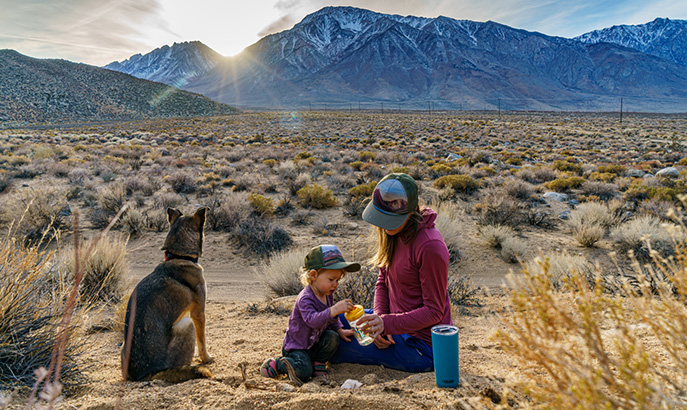 Woman, child and dog sitting in the desert.