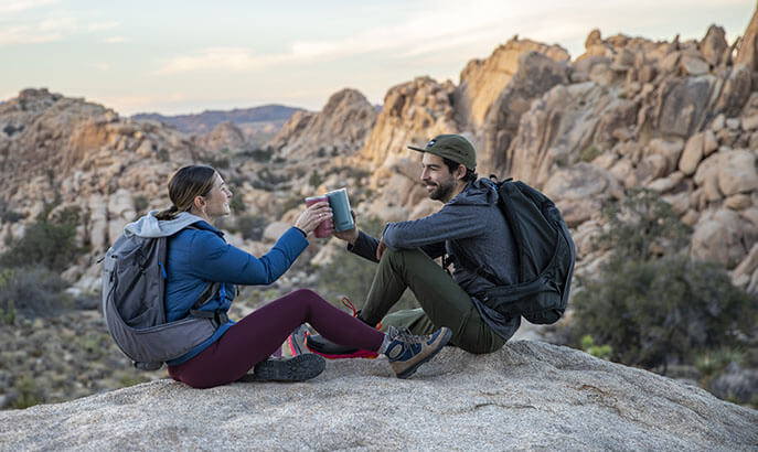 Two people sitting on a mountain wearing a backpack.