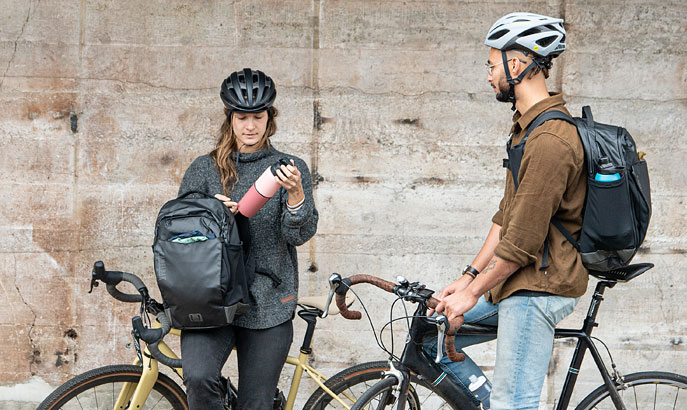 Man and Woman on bikes wear Commute Back Packs.