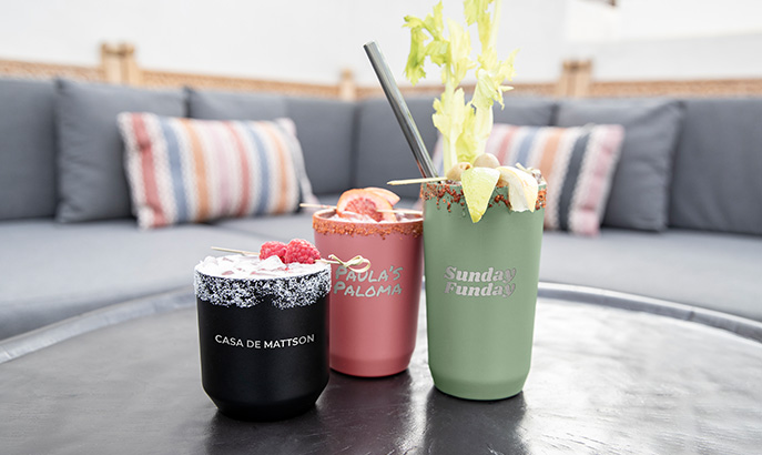Three drinkware tumblers lined up with different laser engraved images and text.
