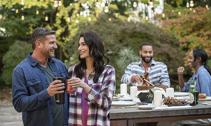A couple toasting with drinkware and a couple sitting at picnic table..