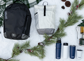 Backpacks, water bottle and drinkware on a snowy background.