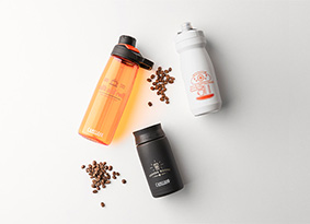 Three customized bottles with coffee beans on white background.