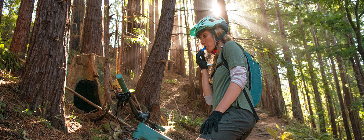 Woman biking in the woods and drinking from a hydration pack.