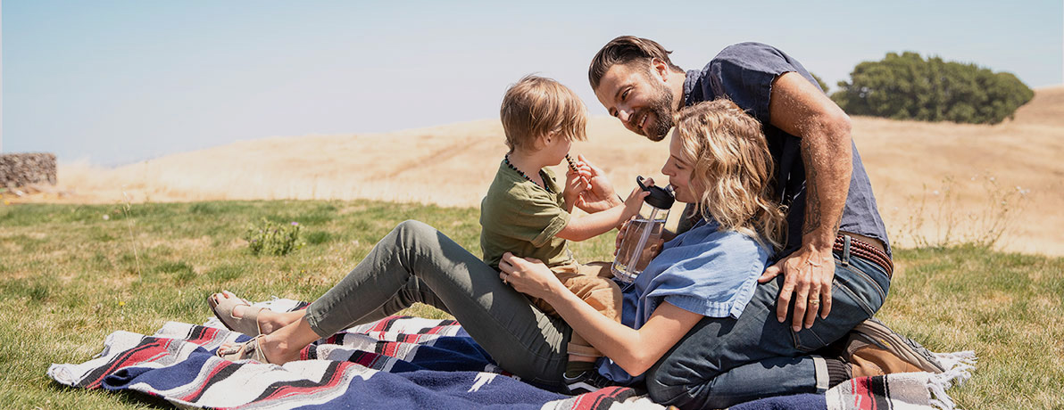 Family on Blanket sipping from water bottles.