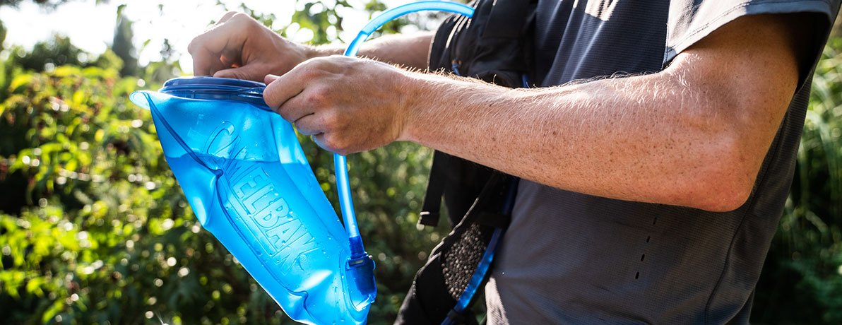 Man sealing hydration pack bladder.
