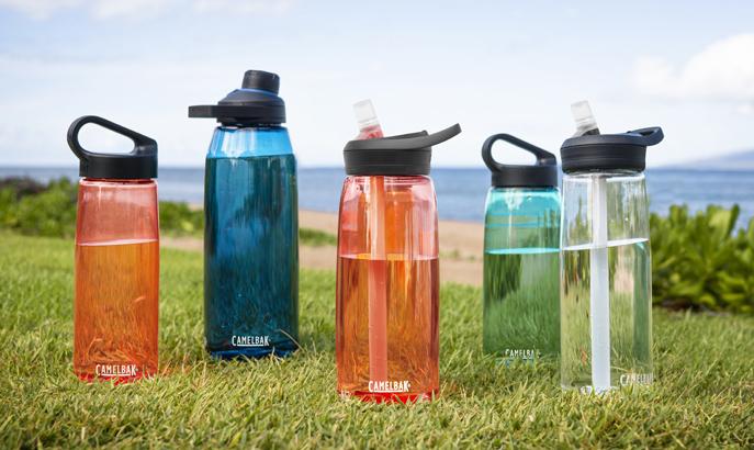 Five Tritan Renew bottles on the grass.