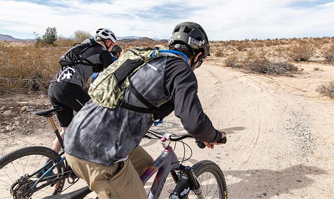 Two Mountain Bikers wearing hydration packs.