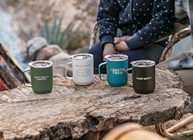 Four custom etched camp mugs on an outdoor surface.