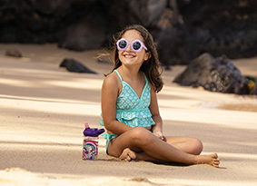 Girl sitting on the beach next to plastic water bottle.