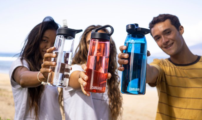 Three people holding plastic water bottles.