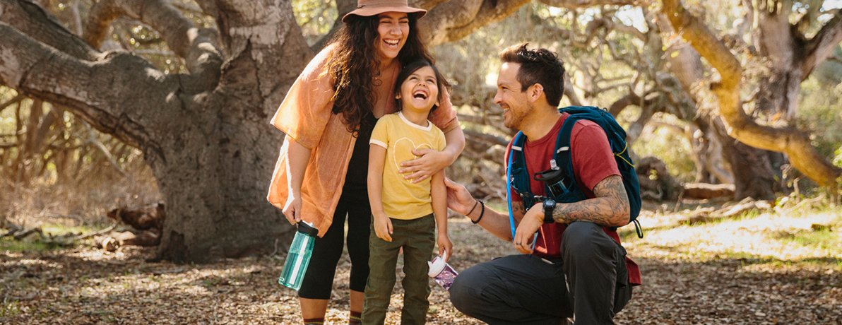 Image of a woman, man and child with water bottles  on a trail outdoors.