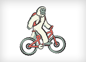 Yeti riding a bike with a hydration pack on.